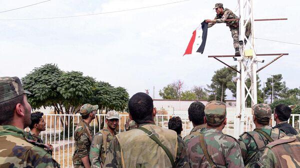 Cирийский солдат, поднимающий сирийский национальный флаг на столбе у границы с Турцией в городе Кобани