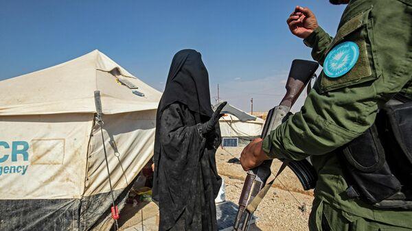 Курдский охранник в лагере для иностранных боевиков и их семей в Сирии