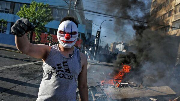 Демонстрант  на горящих баррикадах во время акций протеста в Чили