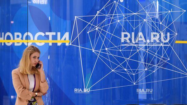 Девушка возле стенда МИА Россия сегодня на Московском международном форуме Открытые инновации