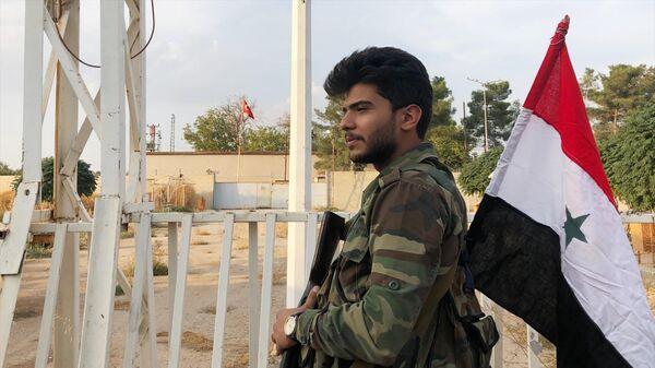 Военнослужащий сирийской правительственной армии на контрольно-пропускном пункте на сирийско-турецкой границе в городе Айн-аль-Араб (Кобани)