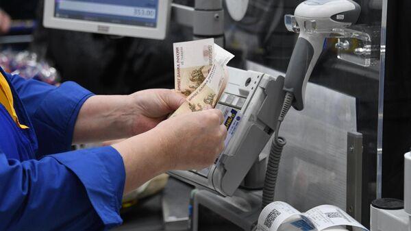 Кассир считает деньги в супермаркете сети Лента в Москве.
