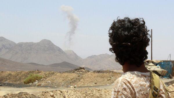 Повстанец в провинции Мариб смотрит на дым поднимающийся от взрыва