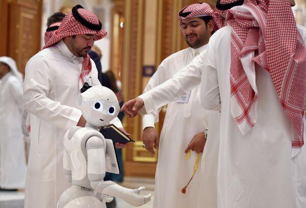 Участники форума Инвестиционная инициатива будущего общаются рядом с роботом в конференц-центре Короля Абдулазиза