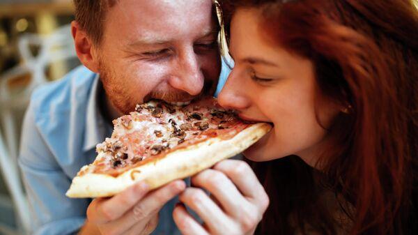 Пара ест пиццу