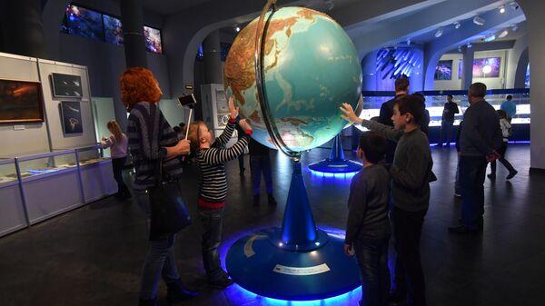 Посетители у глобуса Земли в музее Урании Московского планетария