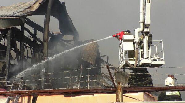 Сотрудники МЧС России во время ликвидации пожара в производственно-складских помещениях в Кемерово. Стоп-кадр видео МЧС России