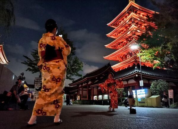 Девушки фотографируются на фоне Буддистского храма Асакуса Каннон в Токио