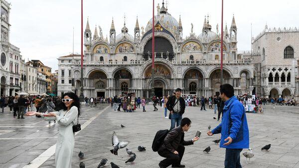 Туристы фотографируются с голубями перед собором Сан-Марко в Венеции