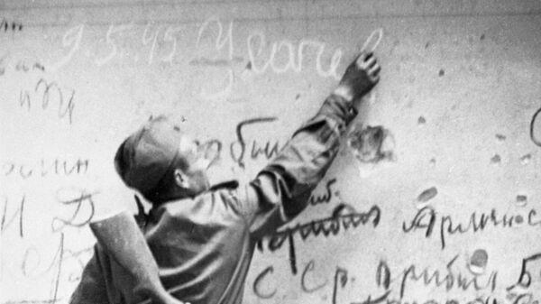 Советский боец Егор Усачев делает памятную надпись на стене Рейхстага.