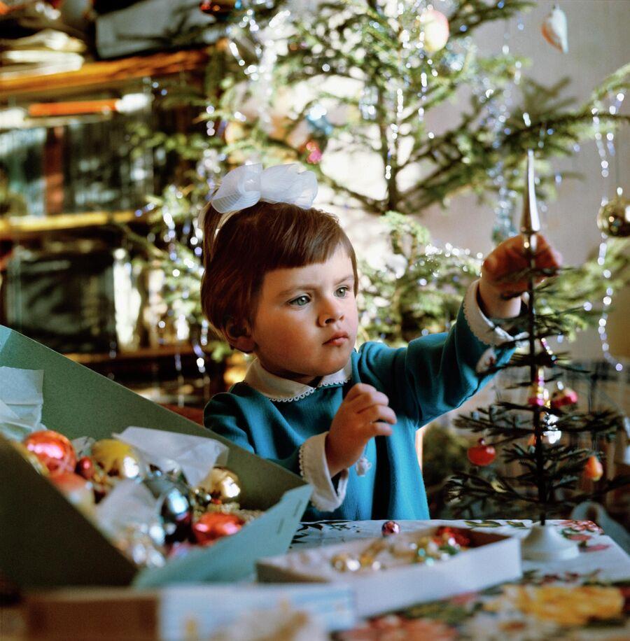 Девочка украшает елку