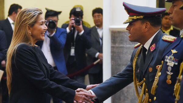 Временный президент Боливии Жанин Аньес пожимает руку новому главнокомандующему вооруженными силами генералу армии Карлосу Орельяне в президентском дворце в Ла-Пасе. 13 ноября 2019