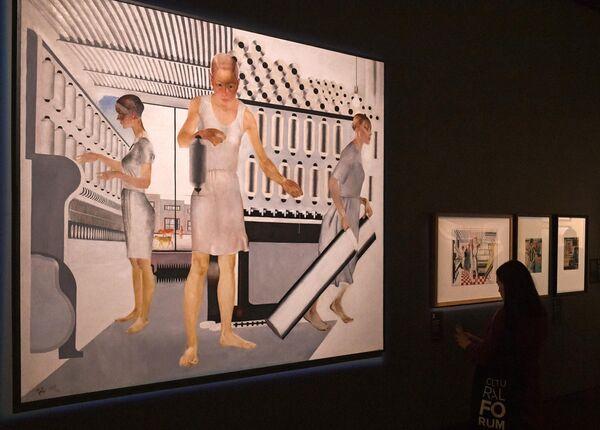 Девушка возле картины Александра Дейнеки Текстильщицы (1927 г.) на выставке Дейнека/Самохвалов в рамках VIII Санкт-Петербургского международного культурного форума в центральном выставочном зале Манеж в Санкт-Петербурге.