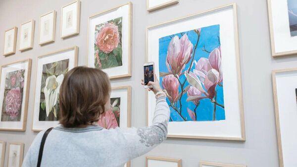 Посетительница выставки фотографирует одну из работ