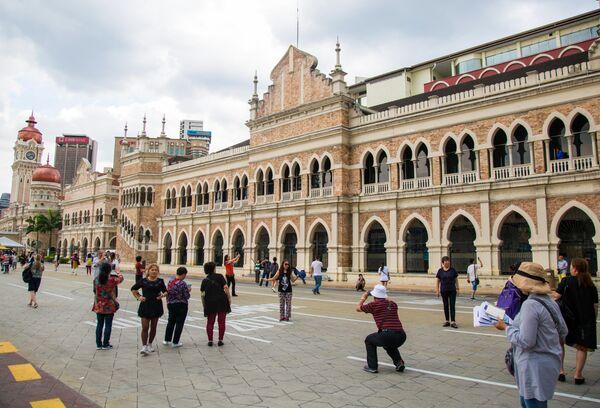 Туристы фотографируются на площади Мердека у здания султана Абдул-Самада в Куала-Лумпуре