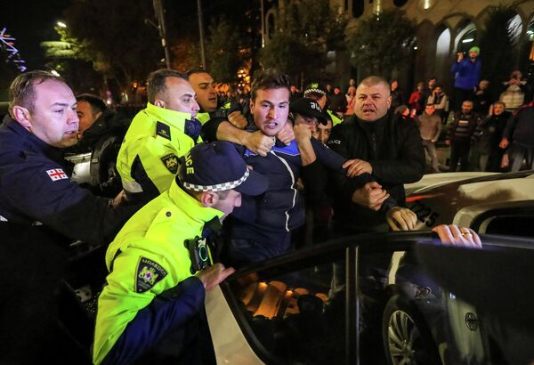 Сотрудники полиции задерживают сторонника оппозиции во время акции протеста в Тбилиси