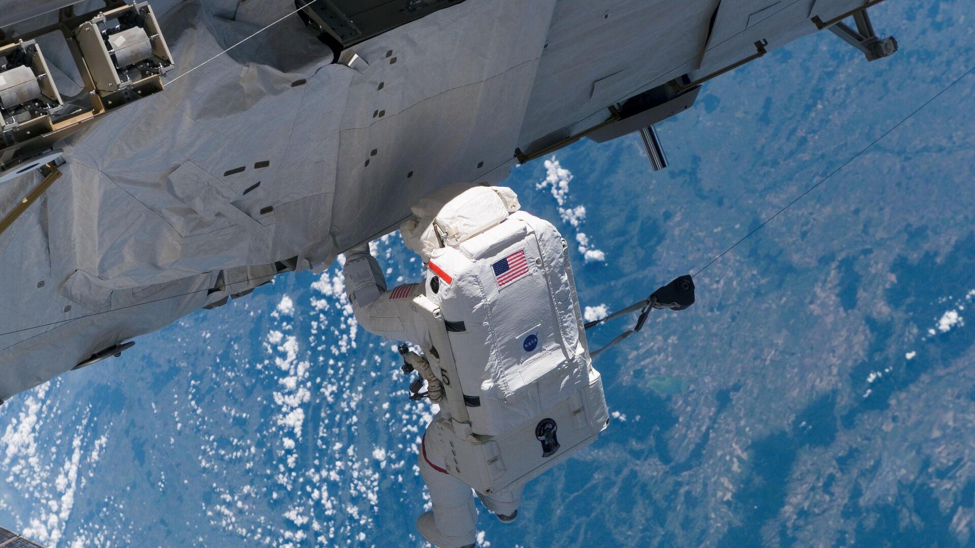 Американский астронавт во время выхода в открытый космос на МКС - РИА Новости, 1920, 08.09.2020