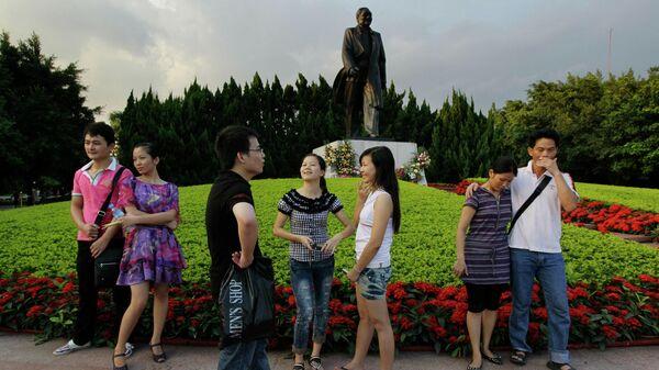 Люди перед памятником Дэн Сяопину в парке в Шэньчжэне, Китай