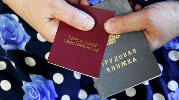 Пенсионерка держит трудовую книжку и пенсионное удостоверение