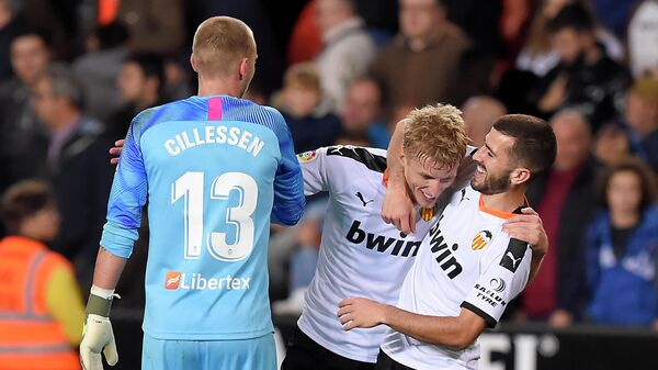 Valencia's Dutch  goalkeeper Cillesen (L), Valencia's Danish midfielder Daniel Wass and Valencia's Spanish defender Jose Gaya celebrate at the end of the Spanish league football match between Valencia CF and Villarreal CF at the Mestalla stadium in Valencia on November 30, 2019. (Photo by JOSE JORDAN / AFP)