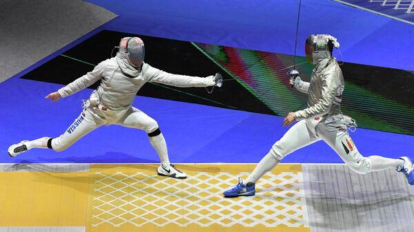 Слева направо: Вениамин Решетников (Россия) в поединке против Матьяша Сабо (Германия) в командных соревнованиях на саблях среди мужчин на чемпионате мира по фехтованию в Будапеште