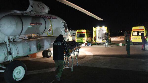 Сотрудники службы медицины катастроф транспортируют пострадавшего в ДТП с пассажирским автобусом в Забайкальском крае