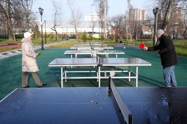 Отдыхающие играют в настольный теннис на территории Детского Черкизовского парка в Москве