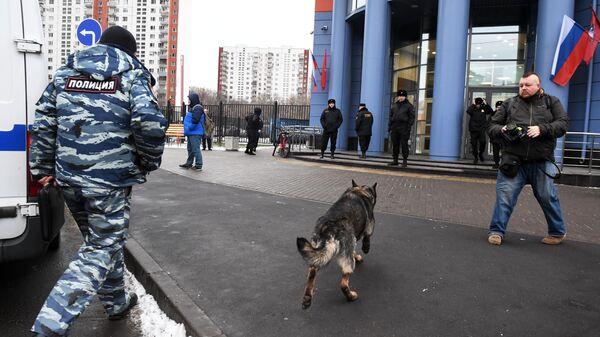 Сотрудник полиции со служебной собакой у здания Тверского суда Москвы, в котором проходит эвакуация в связи с получением анонимного сообщения о заложенном в здании взрывном устройстве