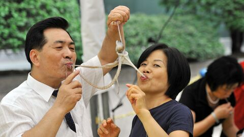 Южнокорейский мужчина и женщина едят живого осьминога на фестиваля еды в Сеуле