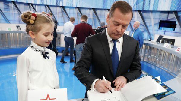 Председатель правительства РФ Дмитрий Медведев оставляет автограф в книге для ведущей канала Карусель Ани Тадыщенко после интервью российским телеканалам