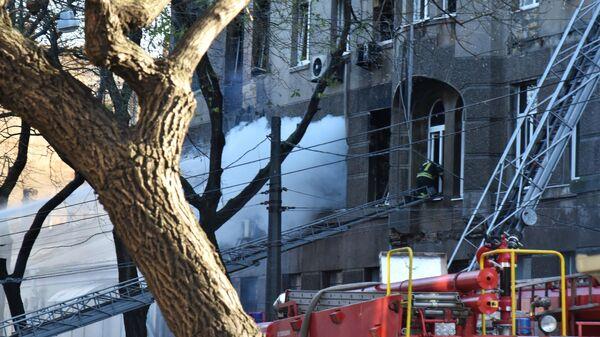 Сотрудник пожарной службы во время тушения пожара в Одесском колледже экономики, права и гостинично-ресторанного бизнеса