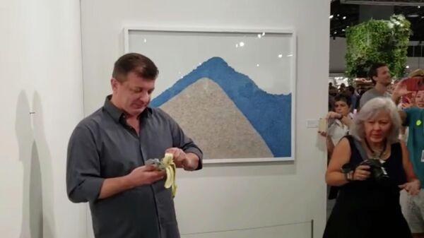 Художник Дэвид Датуна ест работу Маурицио Каттелана на выставке Арт-Базель
