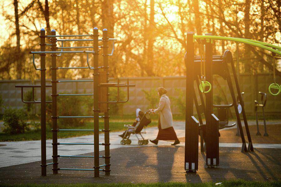 Женщина с ребенком проходит мимо спортивной площадки в Капотне