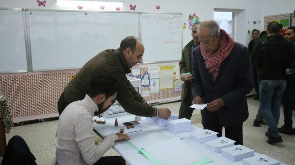 Избиратель получает бюллетени на избирательном участке во время президентских выборов в Алжире. 12 декабря 2019