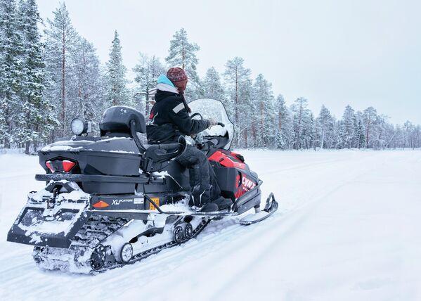 Женщина катается на снегоходе по замерзшему озеру в Рованиеми, Финляндия