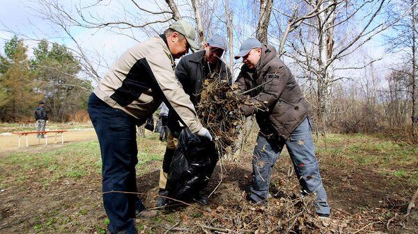 Мужчины убирают листву в пакеты в парке