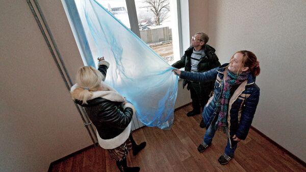 Жители Владивостока осматривают квартиру в новом доме, построенном по программе переселения людей из аварийного жилья