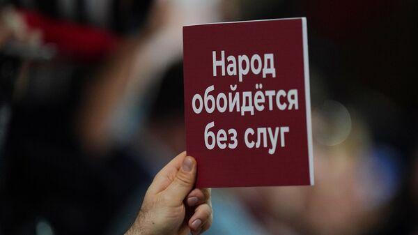 Плакат в руке журналиста, участвующего в большой ежегодной пресс-конференции президента РФ Владимира Путина