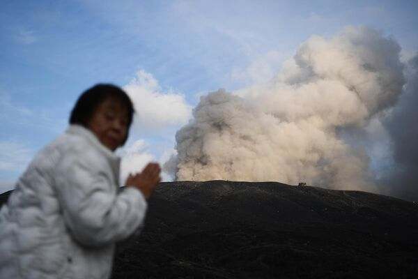 Женщина стоит возле действующего вулкана в городе Асо в префектуре Кумамото