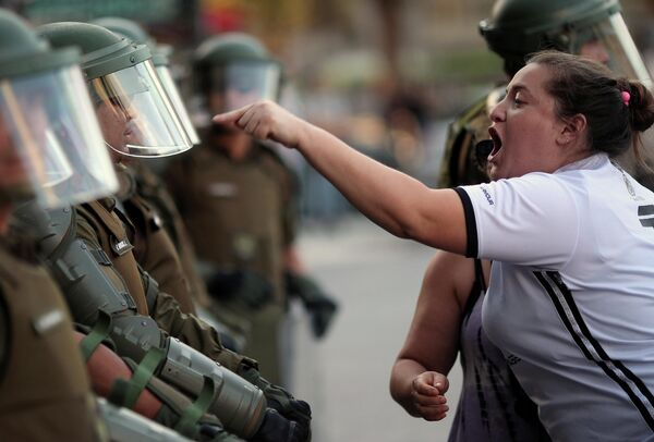 Женщина спорит с сотрудником ОМОНа во время протестов в Чили