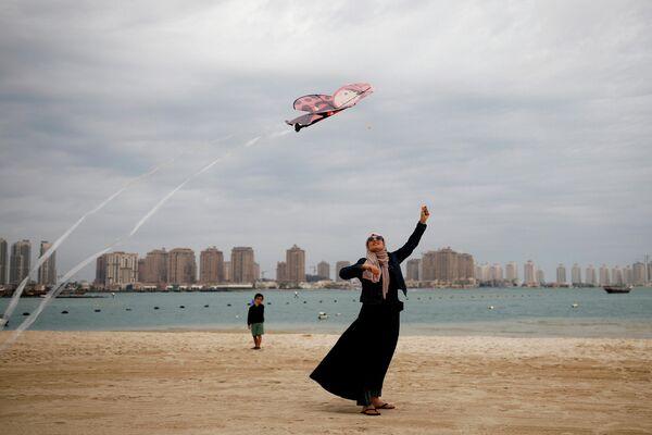Девушка с воздушным змеем на пляже в Дохе, Катар