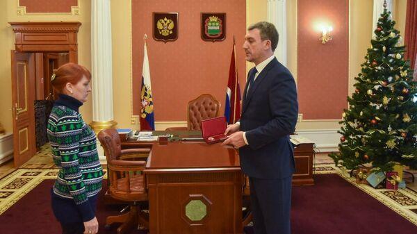 Губернатор Амурской области Василий Орлов вручает медаль За спасение погибавших Марине Пачикиной