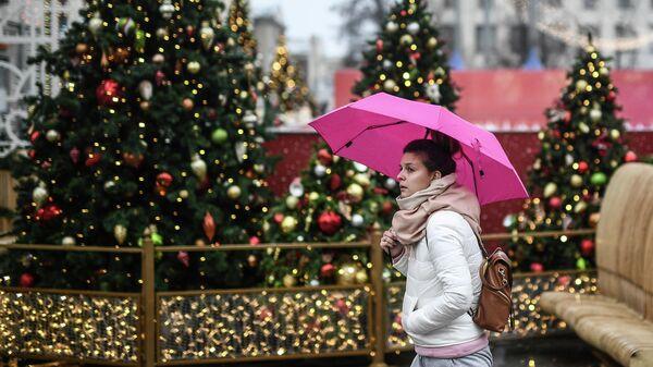Девушка идет под зонтом по улице Москвы