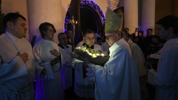Викарный епископ Юрий Кособуцкий вносит младенца в рождественский вертеп в римско-католическом кафедральном соборе Святого Имени Пресвятой Девы Марии в Минске