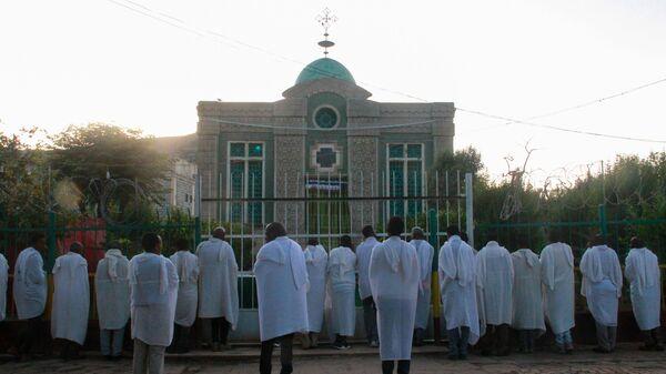 Эфиопские христиане молятся у ворот храма Девы Марии Сионской, где хранится Ковчег Завета. Аксум, Эфиопия