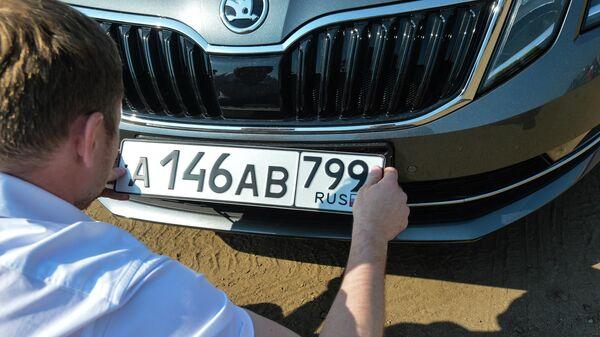 Автовладелец устанавливает номерной знак на автомобиль
