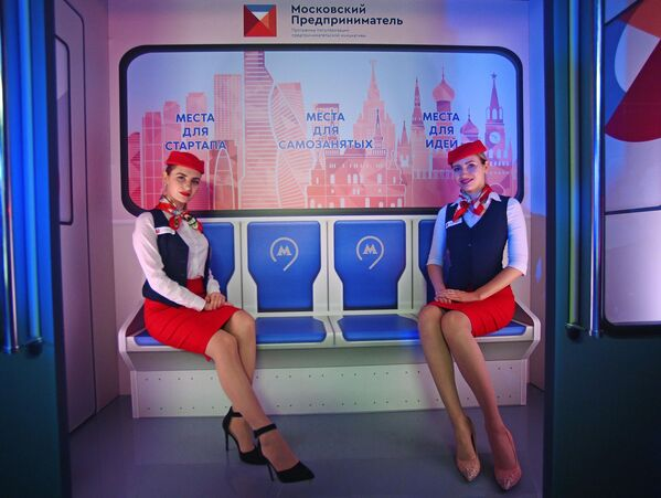 Модели в форме сотрудниц Московского метрополитена на фоне инсталляции, приуроченной к запуску тематического поезда Московский предприниматель