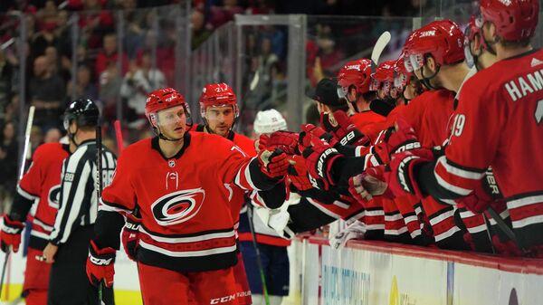 Центровой форвард Каролины Лукас Уолмарк празднует гол с партнерами по команде в матче НХЛ против Вашингтон Кэпиталз