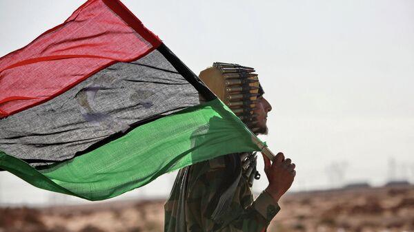 Боец оппозиции с флагом Ливии