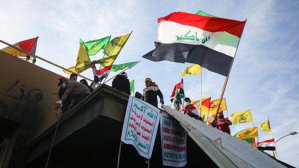 Сторонники сил народной мобилизации Ирака во время демонстрации против нанесения авиаударов у посольства США в столице Ирака Багдаде. 1 января 2020